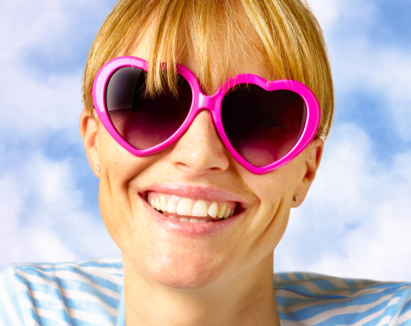 Woman in heart shaped glasses smiling